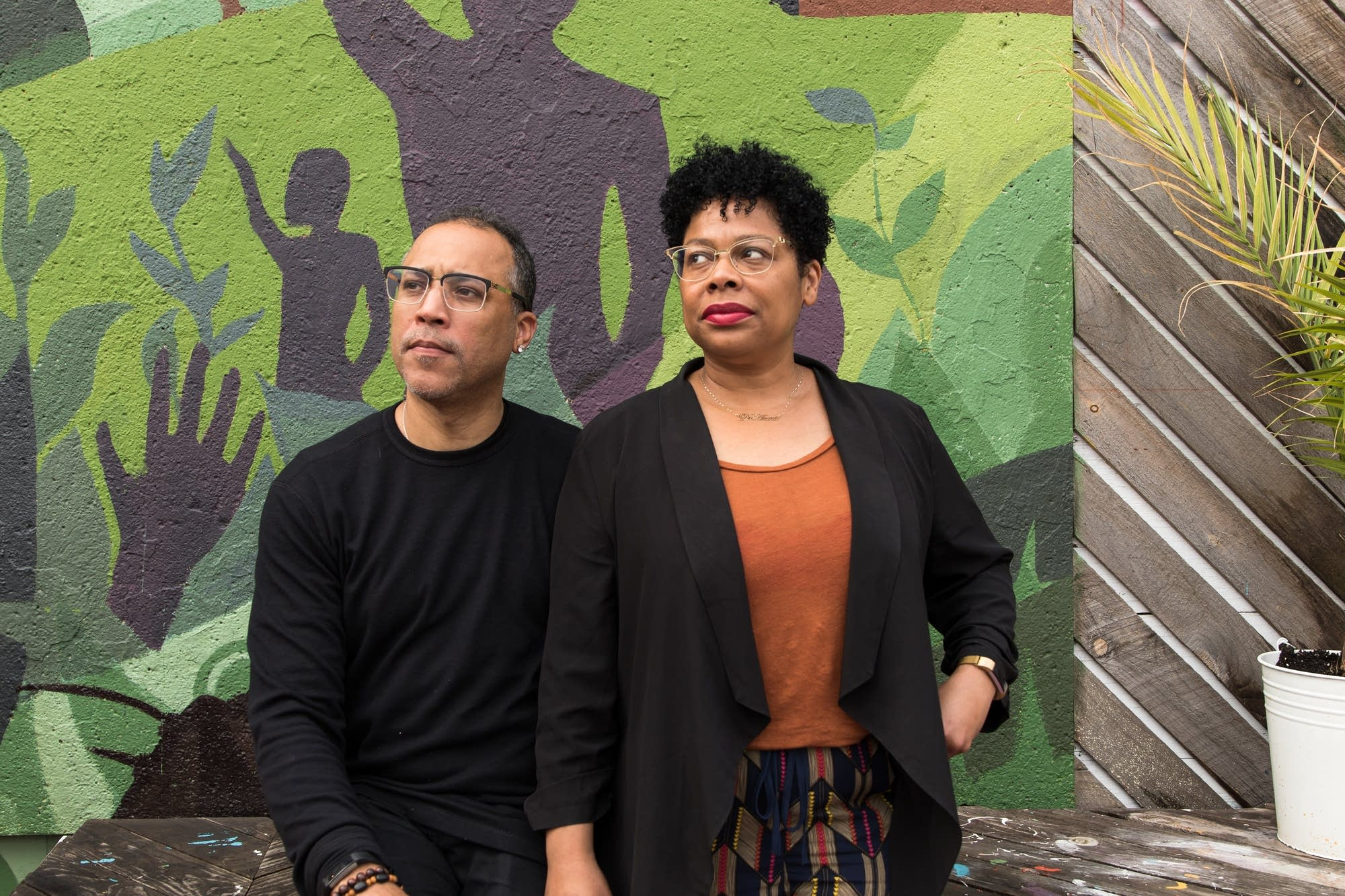 Roger and DeAnna Cummings pose for a portrait in front of a mural.