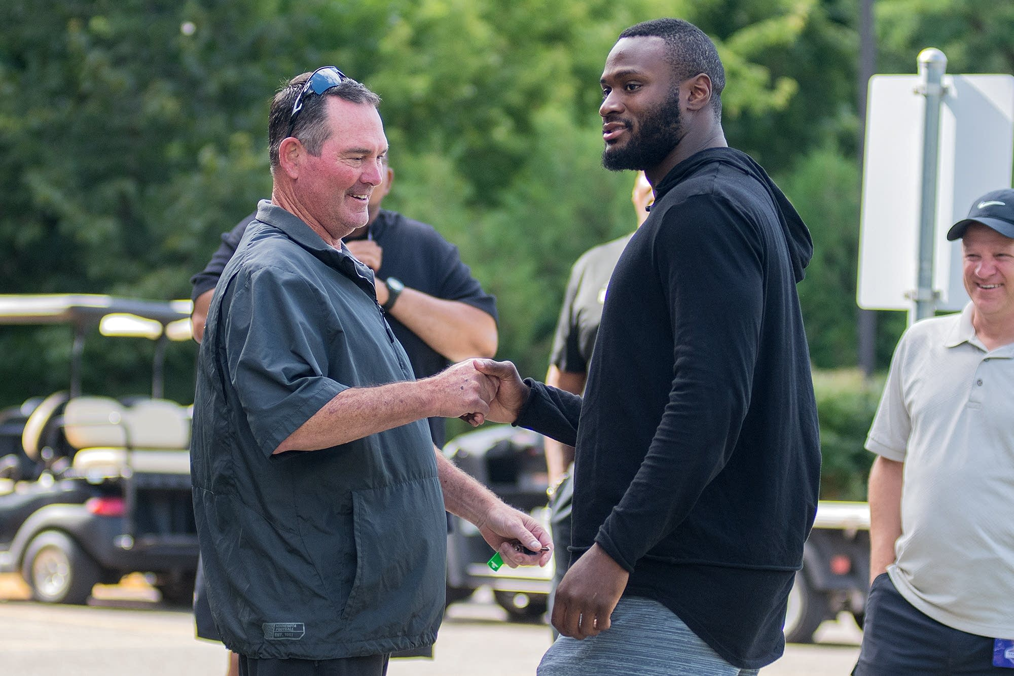 Head coach Mike Zimmer shakes hands with running back Latavius Murray.