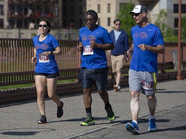 "Kristin Haskell, Darin ""Wes"" Weston and Matt Schumacher run in a 5K race."