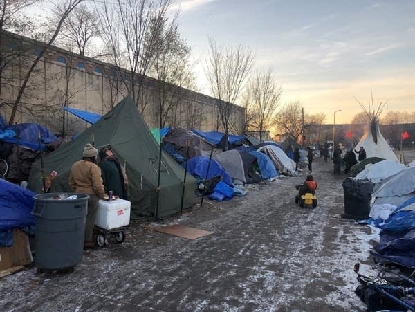 Residents of Minneapolis's homeless encampment erect arctic tents.