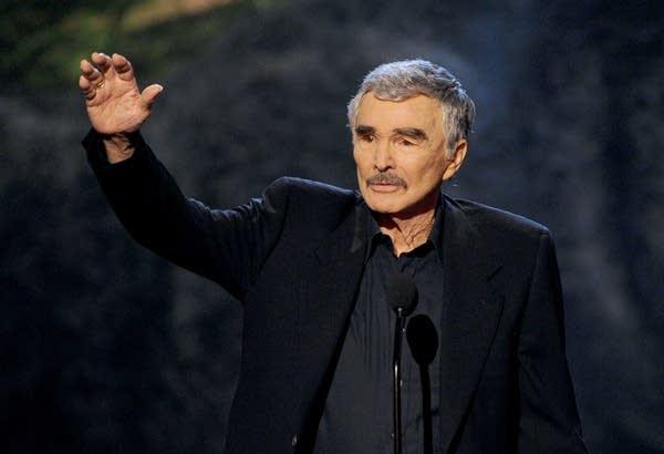 Actor Burt Reynolds accepts an award onstage.