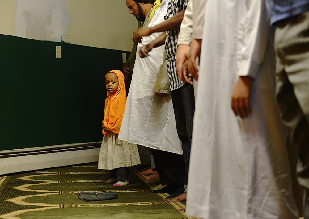 Girl peeks out during prayer