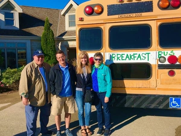 """4 people in front of a school bus with a sign that reads """"breakfast bus"""""""