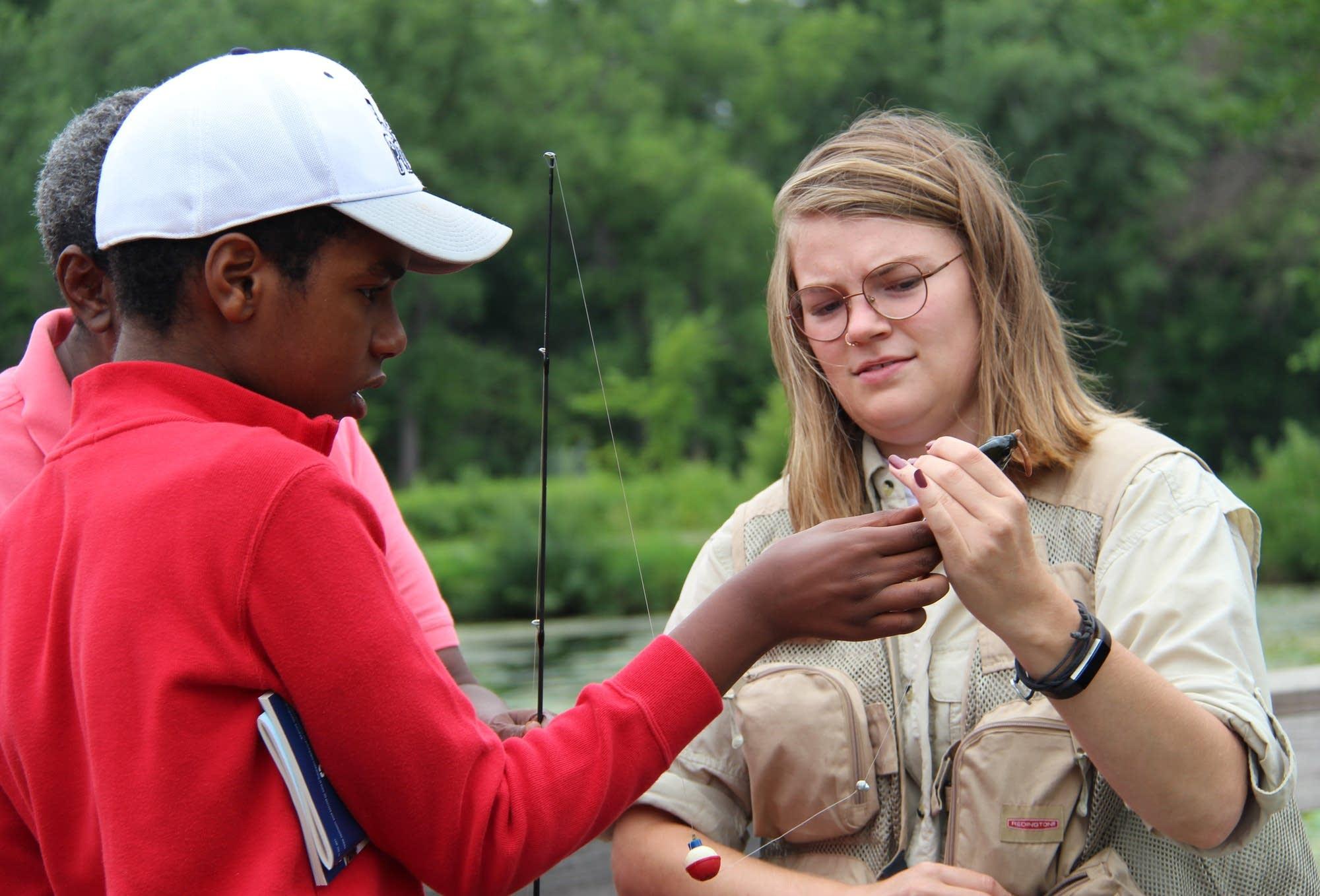 MinnAqua Intern Gabby Travers, right, helps Ishmael Diriye remove a fish.