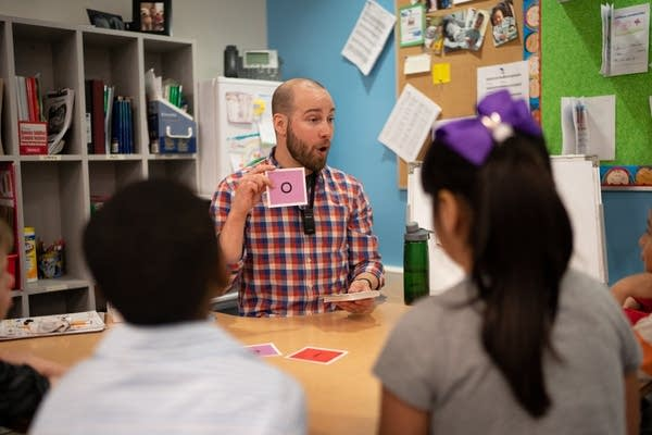 Kindergarten teacher Matt Proulx teaches pronunciation of Spanish vowels.