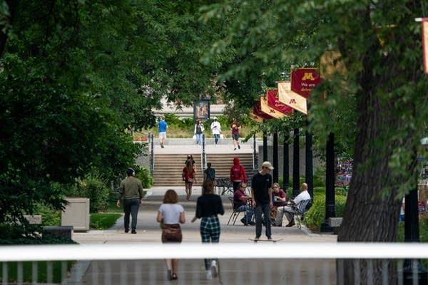 People walk down an outdoor corridor.