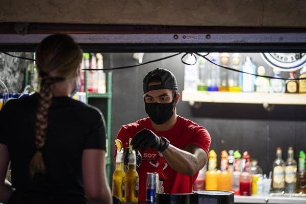 A man prepares drinks at a bar in Mankato.