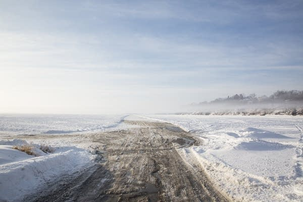Fog floats over a plowed ice road onto Cooks Bay