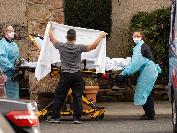 Health-care workers transport a patient on a stretcher
