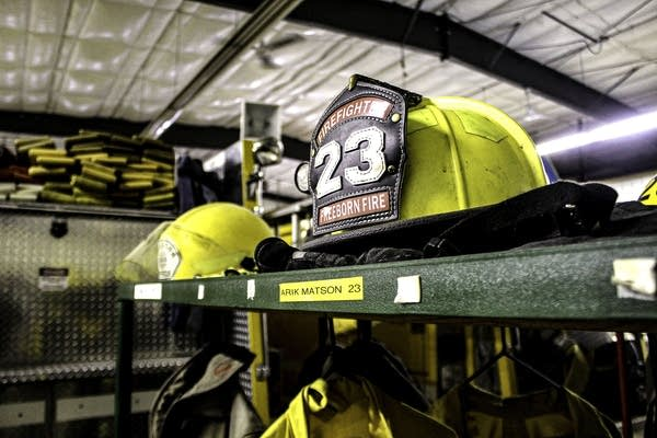 A yellow firefighter hat on top of a metal locker.