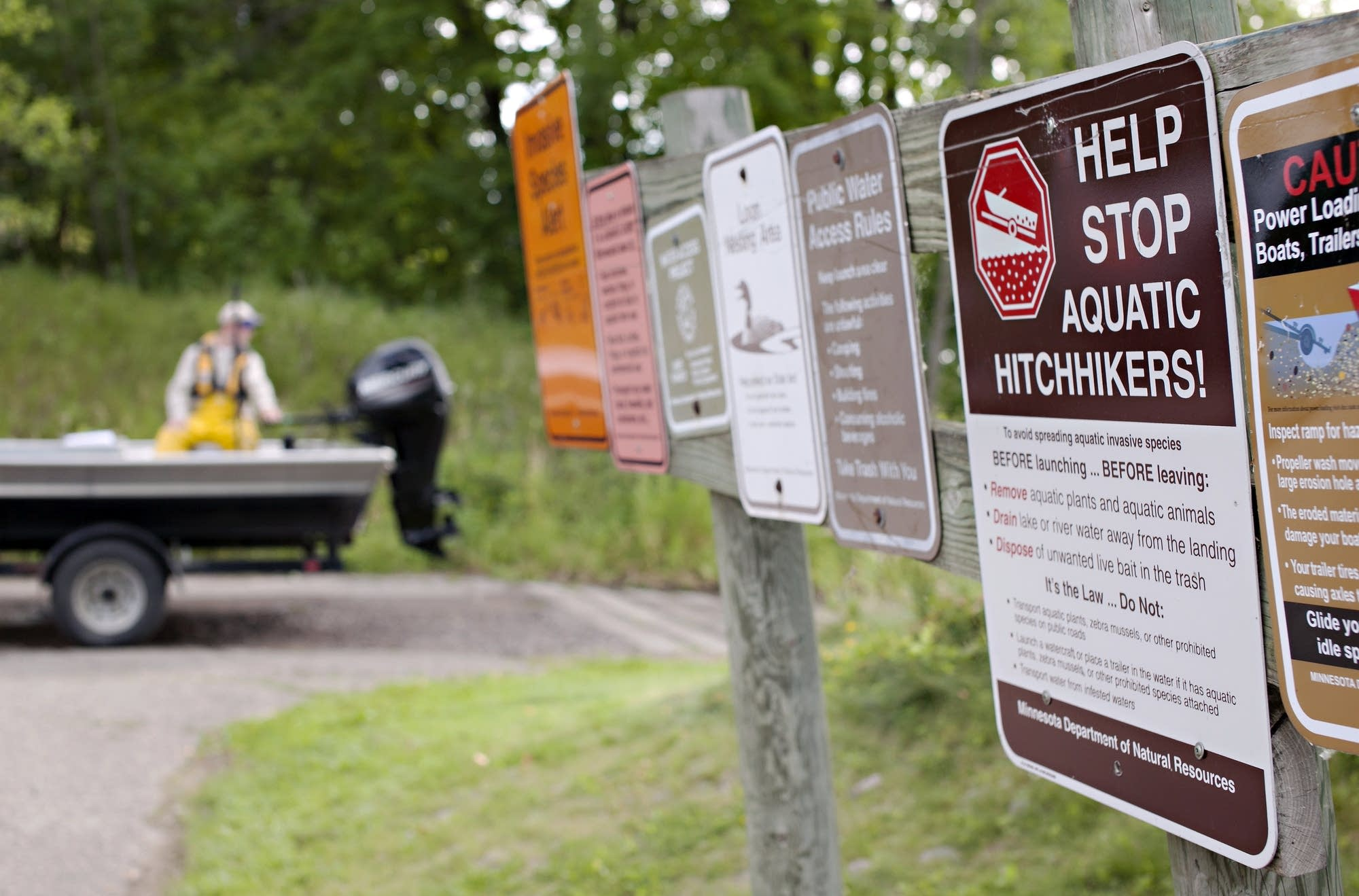 Reminders about invasive species are posted at a public boat launch.