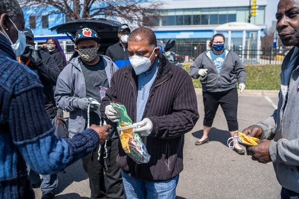 A man in a mask hands out cloth masks to others.