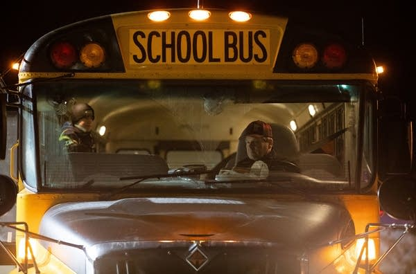 A man sits in the driver seat of a bus at night