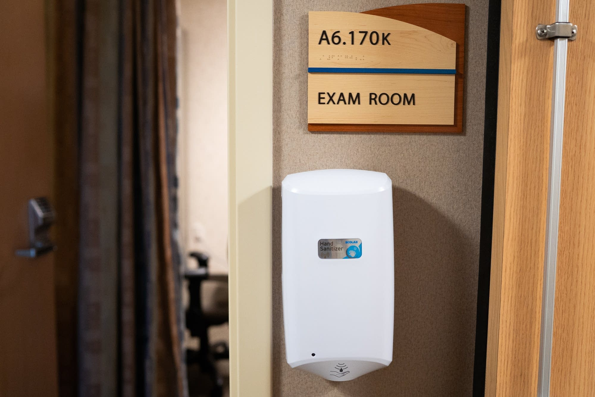 An automated hand sanitizer station hangs outside of an exam room