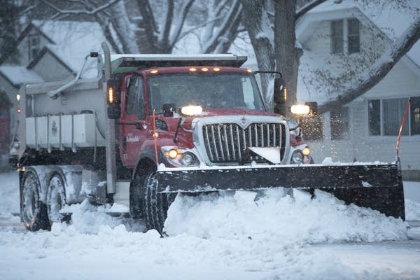 A snowplow pushes snow down a road.