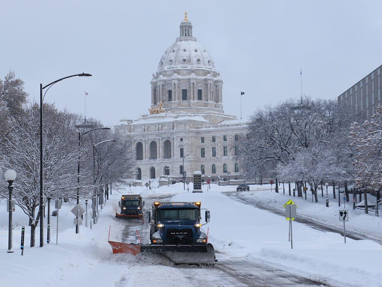 Snow plows make their way down Cedar Street in St. Paul.