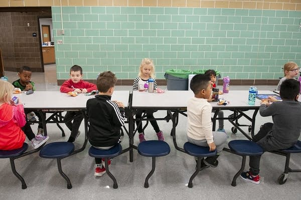 Children sit at a lunch table.