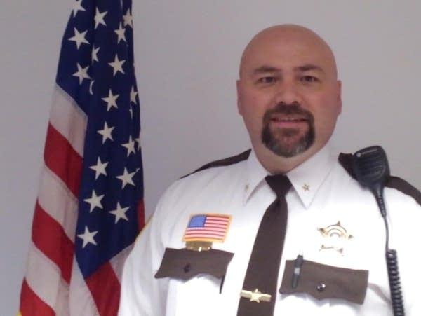 A man in an officer's uniform stands next to a U.S. flag.