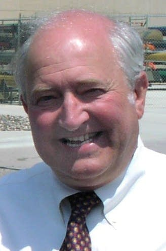A man wearing a shirt and tie smiling at the camera