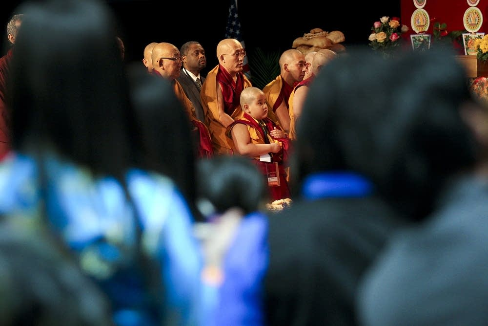Monks and lamas stand to honor the Dalai Lama.