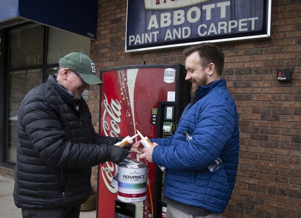 A man hands another man a can of paint while standing outside a store.