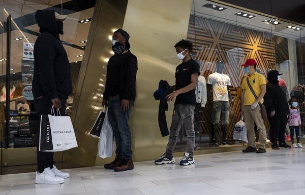 People wearing masks line up outside a store