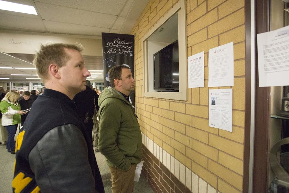 Caucus-goers look at candidate fliers.