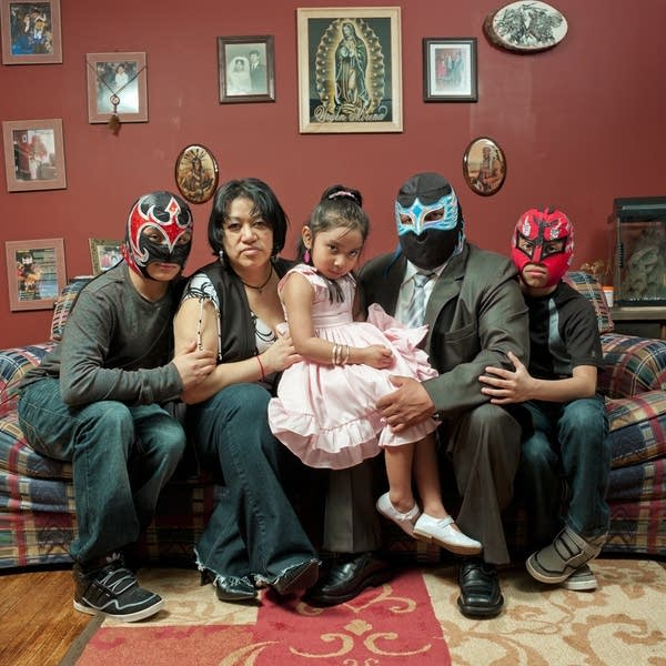Latino family sitting on couch with men the wearing luchadora masks.