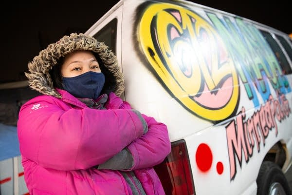 A woman wearing a pink coat and face mask stands outside a van
