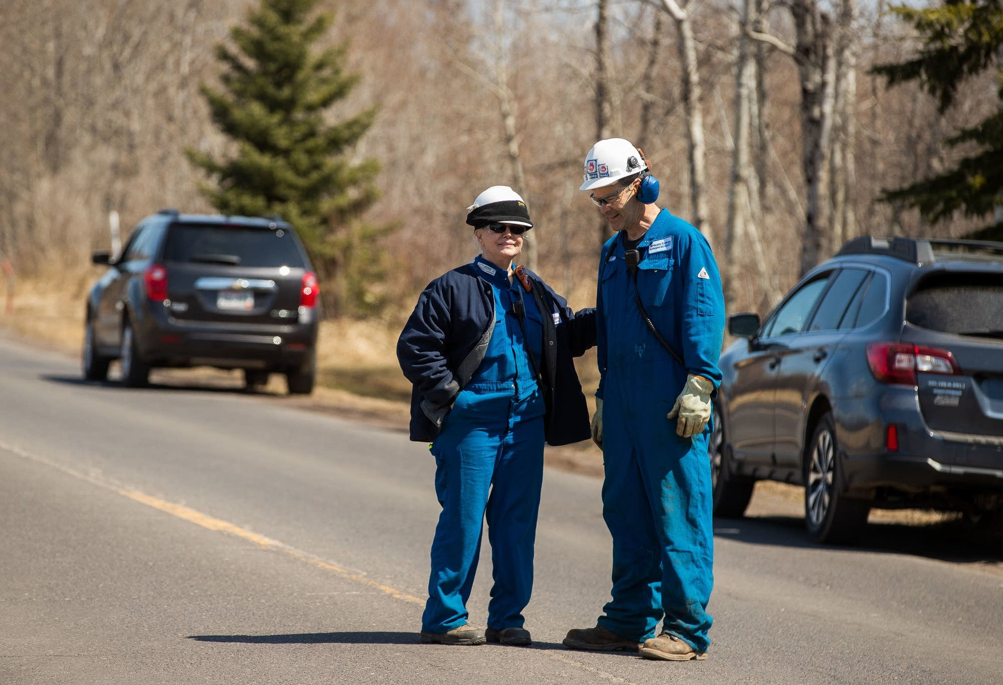 Workers from the Husky Energy oil refinery greet each other evacuating.
