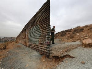A U.S. Border Patrol agent walks past a fence.