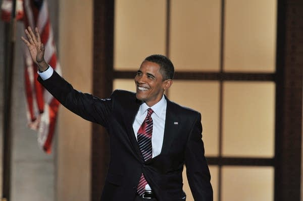 Barack Obama waves to the crowd at Invesco Field