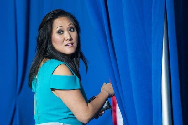 A woman in a teal dress walks behind a blue curtain.
