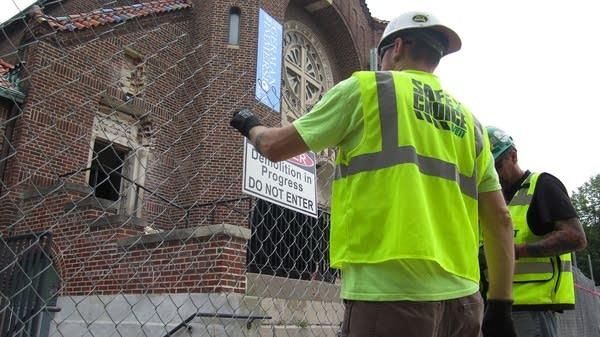"Two workers set up a ""Do Not Enter"" sign in front of the church."