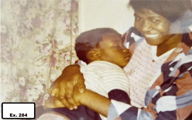 A photo of a woman holding a sleeping child.