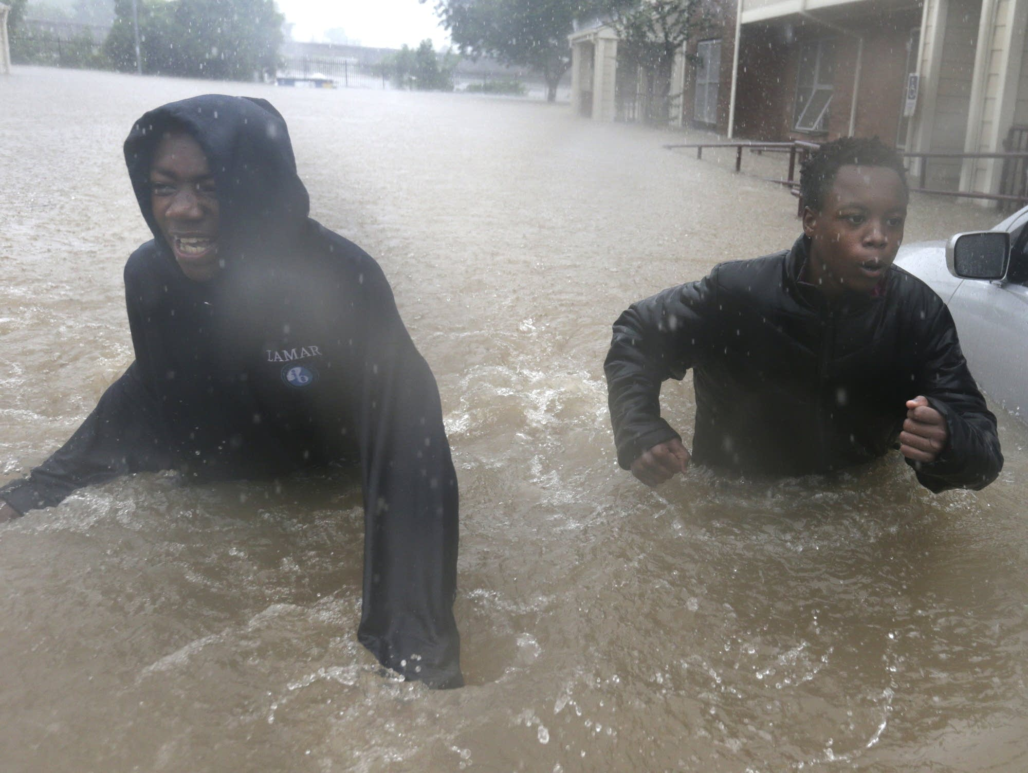 Two friends make their way through floodwaters.