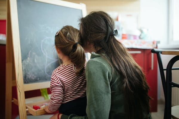A mom and a child in front of a chalkboard.