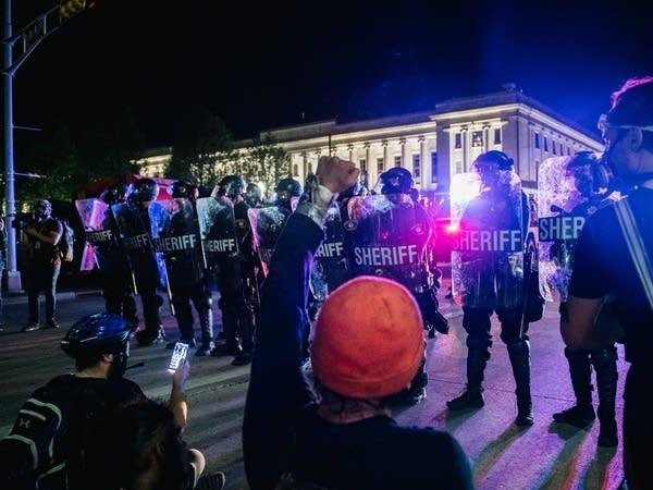 Demonstrators sit in the street, in front of law enforcement.
