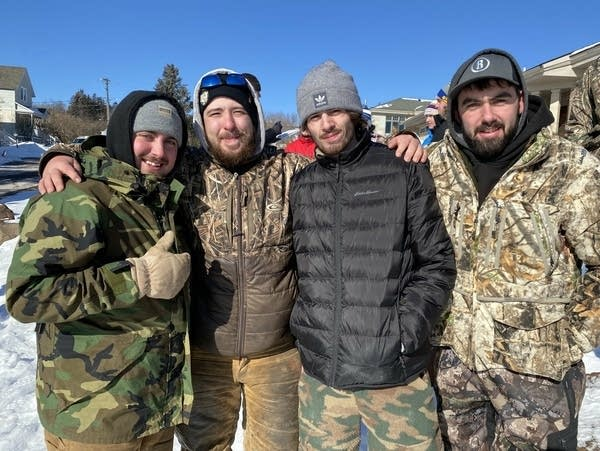Four people in camo and winter gear pose for a photo