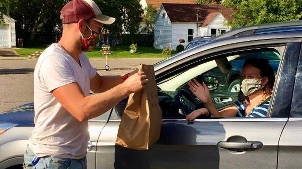 a man hands a bag to a woman in a car