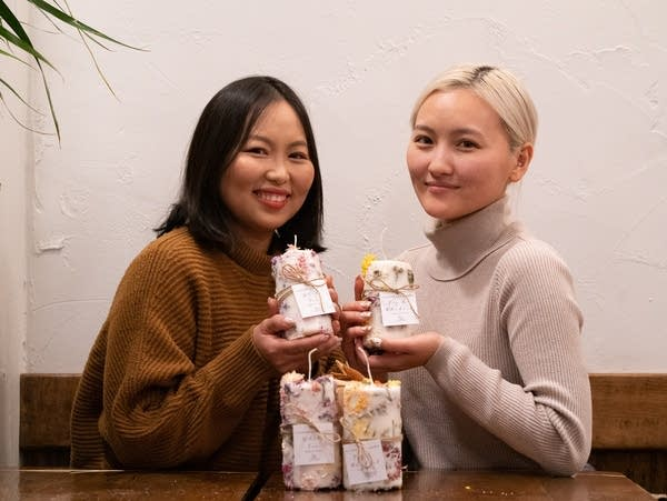 Xee and Pachia Vang show candles made with flowers made from family's farm
