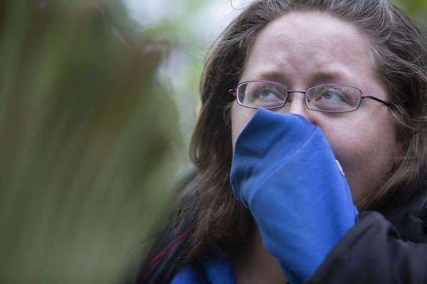 Olivia Sparks of St. Paul holds her nose as she views the corpse flower.