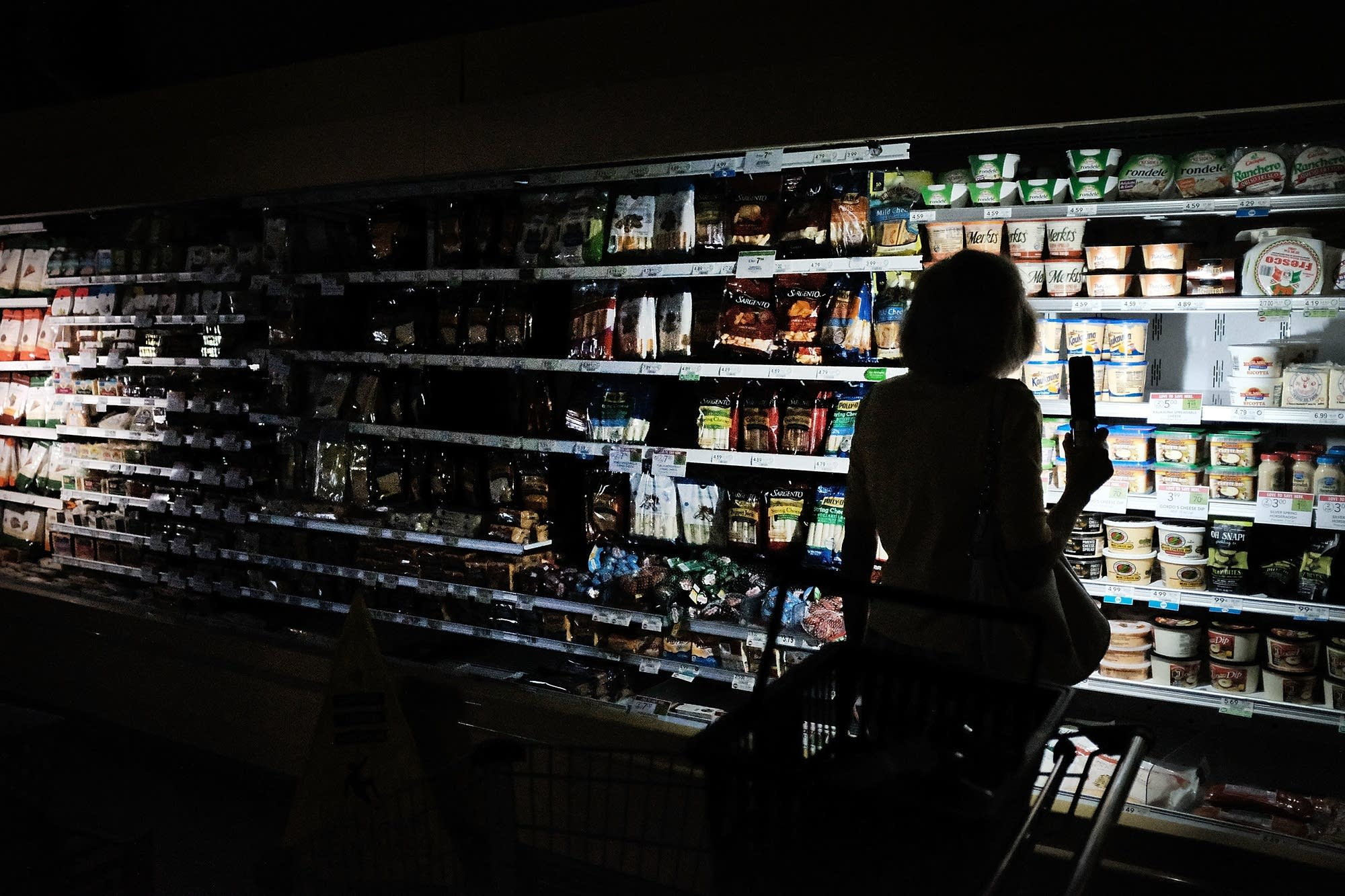 People shop in a supermarket with limited electricity.