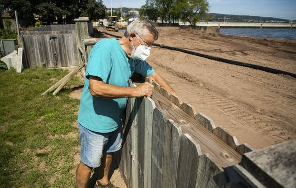 A person leans over a fence that separates his yard and beach.
