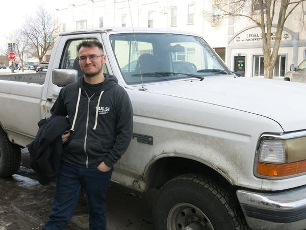 A man leans against a white pick-up truck.