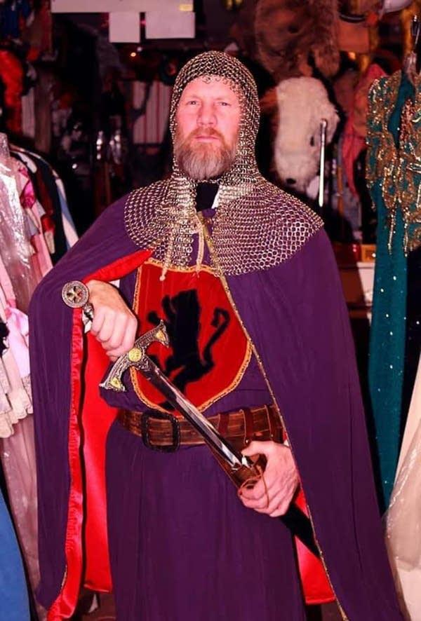 A man wearing a knight costume.