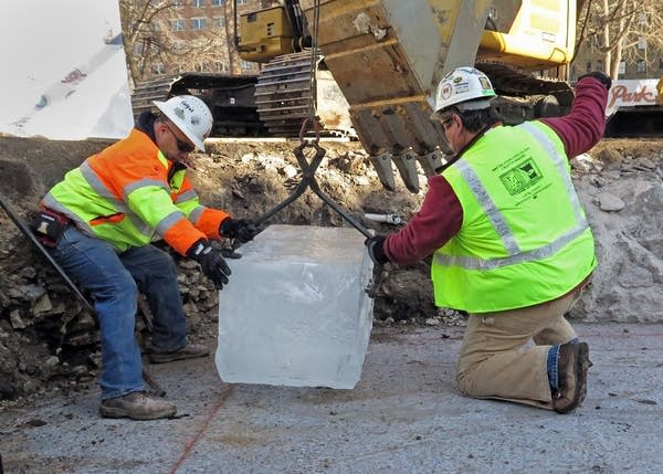 Construction workers lowered a block of ice to start the ice palace.