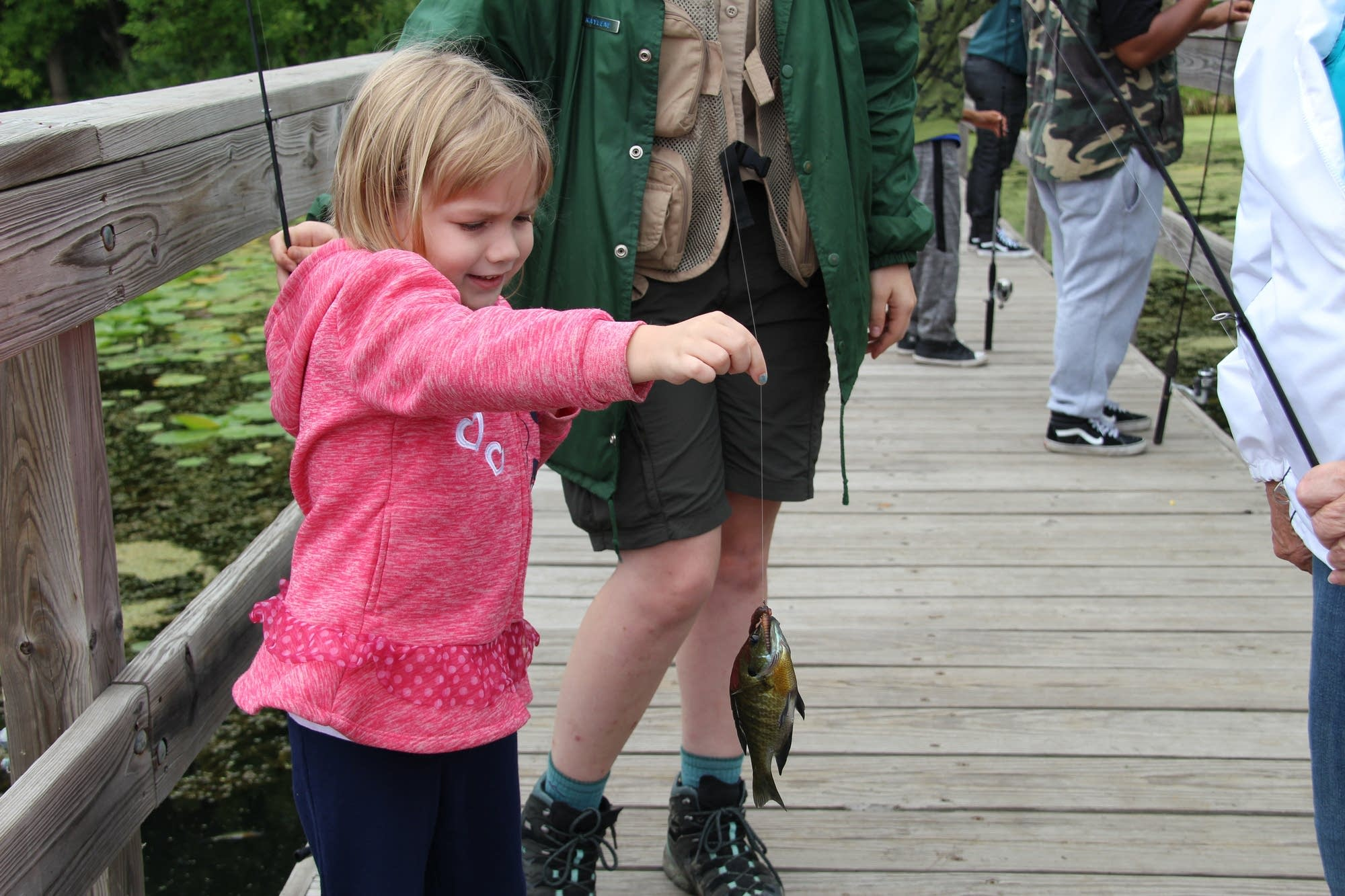 Ceci Montminy holds the fish her grandma just caught at a distance