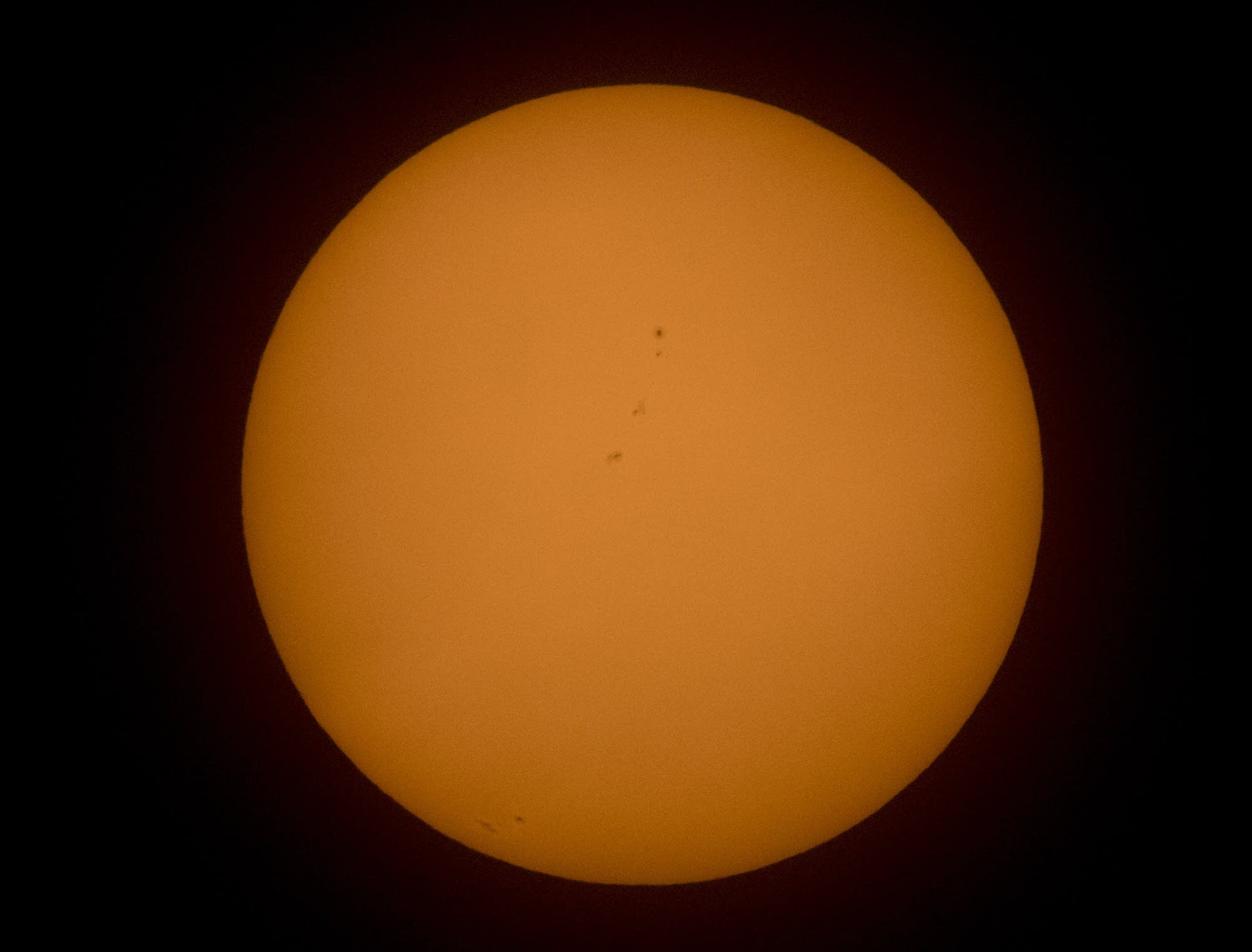Sunspots can be seen on the lower part and center of the sun.