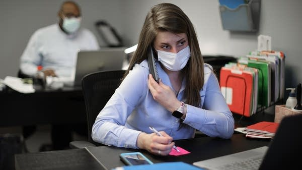A woman with a face mask sits at a desk in an office.